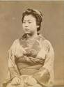 Portrait of a seated Geisha - albumen photograph by unknown photographer 1870's.