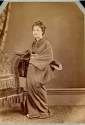 Geisha in traditional dress besides a Western style chair - Japanese photograph 1870's