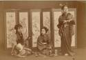 Three girls sitting or standing before a painted screen - Japan
